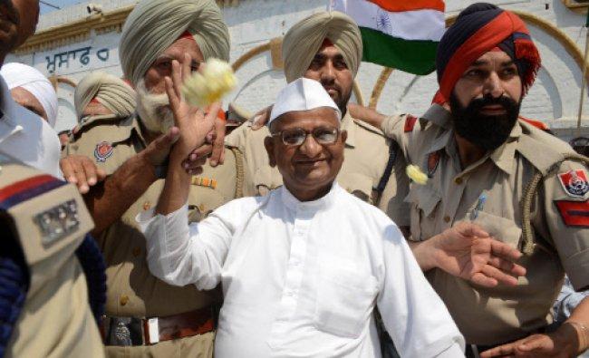 Anti-corruption activist Anna Hazare (C) waves to media representatives as he is escorted...