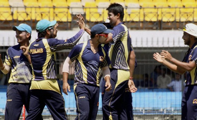 Rahul Sharma of Punjab celebrates with teammates after striking \'hat-trick\' against Uttar Pradesh...