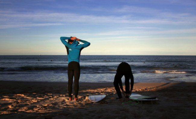 Surfers prepare their wetsuits and boards before entering the water at Sydney\'s Manly Beach...