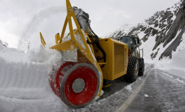 A snow blower clears snow and ice from the mountain pass road leading to the Grimsel Pass...