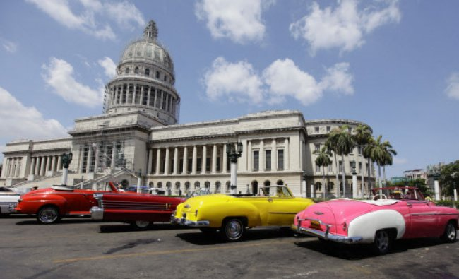 U.S.-made vintage convertible cars are parked beside the Capitol Building in Havana May 15, 2013...