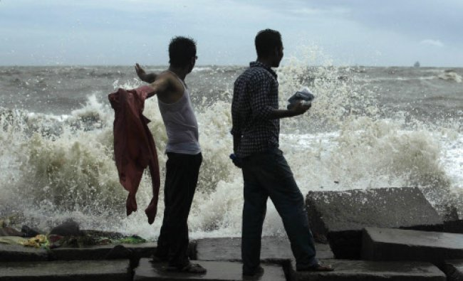 Men stand by the shore of Bay of Bengal before cyclone Mahasen approaches in Chittagong...