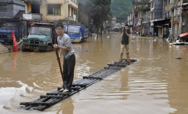 A journalist (R) records a video on a raft as a man paddles along flooded street after heavy...