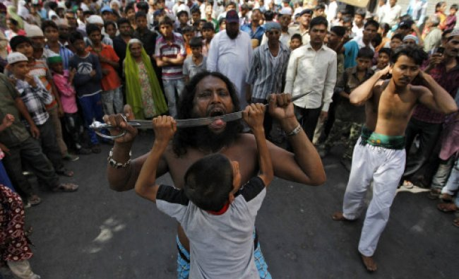 A man performs a stunt during an annual religious procession marking the death anniversary...