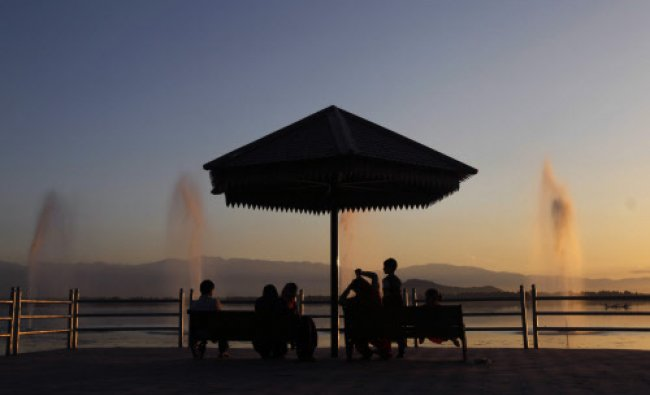 A family sits on a jetty on the banks of the Dal lake as the sun sets in Srinagar...