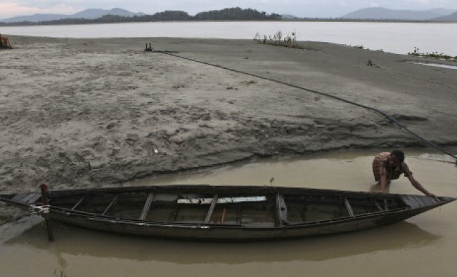 A boatman places his boat at a safer place on the bank of River Brahmaputra, after an alert...