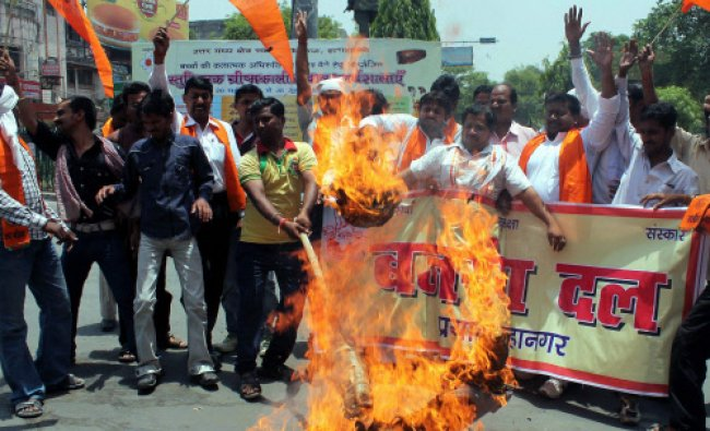 Allahabad: Bajrang Dal Activists burning an effigy of Union government in protest against grant...