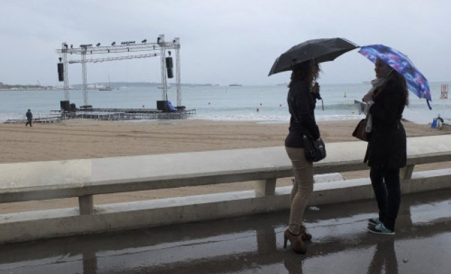 Two women stand on the croisette with umbrellas during rain at the 66th Cannes Film Festival...