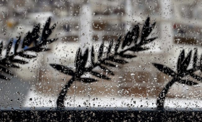 Palme d\'Or symbol metal cutouts are seen through a window of the Festival Palace during heavy rain..