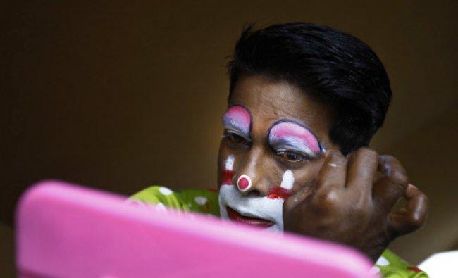 In this April 11, 2013 photo, Biju Nair, principal clown at Rambo Circus applies make-up before...