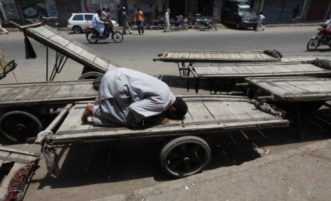 Man offers prayer on a cart, near a mosque, along a road in Karachi...