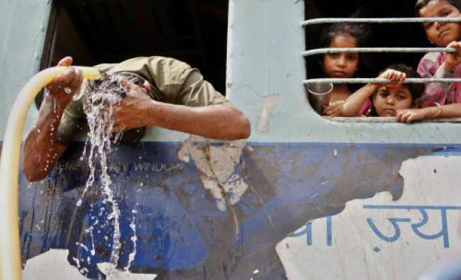 An Indian commuter pours water over his head to cool off as young children watch from a window...