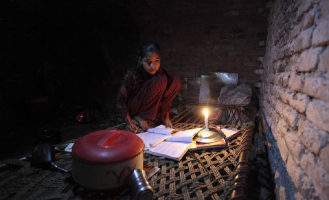 Noreen uses candlelight as she studies during a power outage in a slum in Islamabad...
