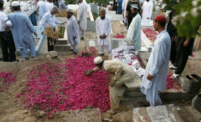 A man places a rose branch on the grave of Zara Shahid Hussain, a senior politician from the...