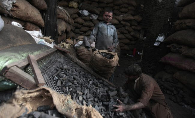 Men sort coal at a wholesale shop to sell in the market in Rawalpindi May 20, 2013.