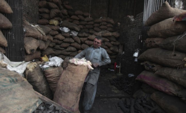 A man carries a sack of coal to weigh it before selling it to the market at a wholesale coal shop...