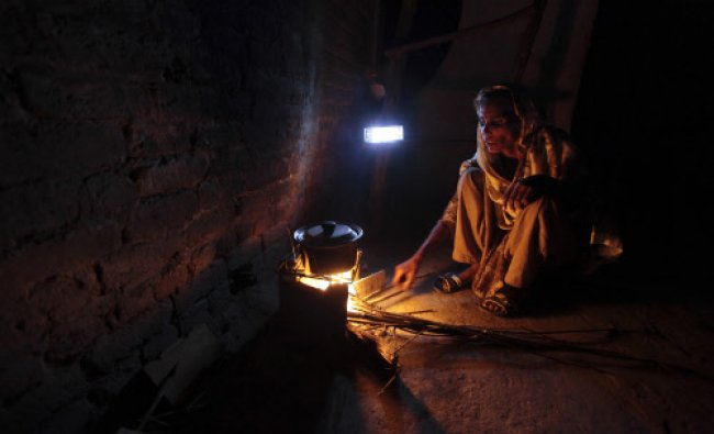 A woman cooks over a wood-burning fire under a battery-run emergency light during a power outage...