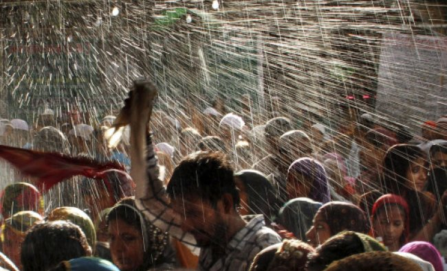 Devotees are showered with perfumed water during the end of the Urs festival, at the shrine...