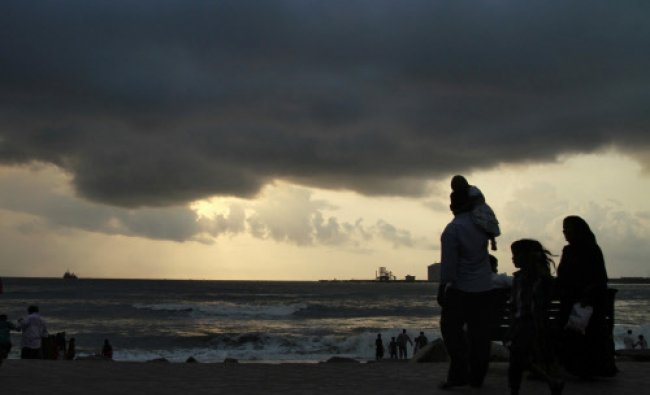 Beachgoers stroll along the Fort Kochi beach as clouds hover over the Arabian Sea in the southern...