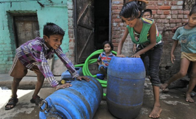 children transport barrels filled with water from a government tanker in New Delhi...