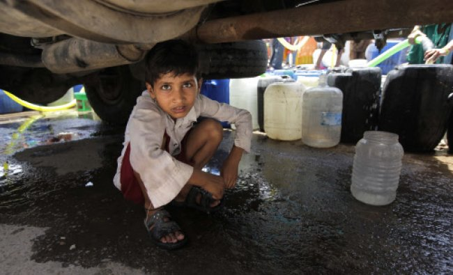 A boy fills a plastic container with water dripping from a government tanker in New Delhi...