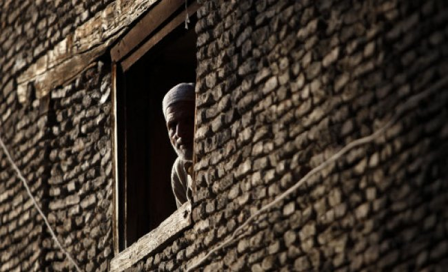 A man looks through the window of his house in downtown Srinagar May 23, 2013. REUTERS