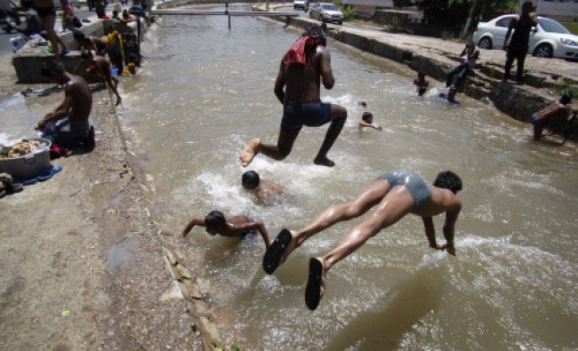 Youth bath in a canal on a hot summer day in Jammu, India, Thursday, May 23, 2013. Severe heat...