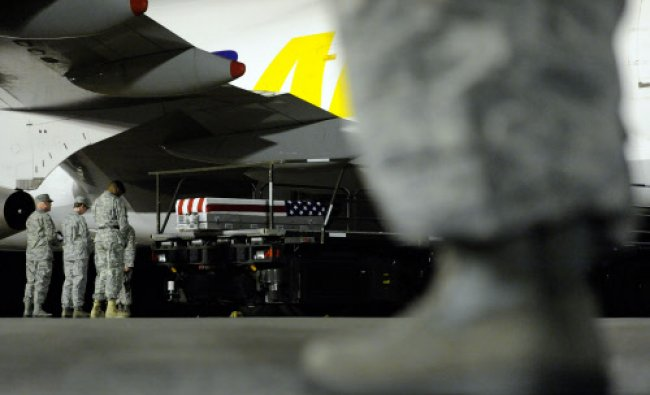 A transfer case containing the remains of Staff Sgt. Joe A. Nunezrodriguez sits on a loader...
