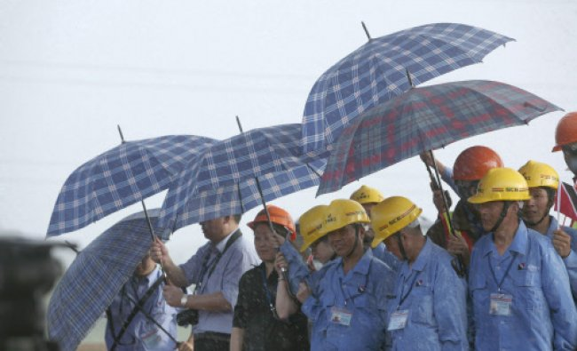 Workers of the Shanghai Construction Group and Chinese media use umbrellas as they take shelter...