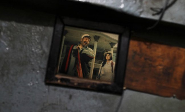 A scene of an old Pashto movie is seen through a window at Arshad cinema in Peshawar ...