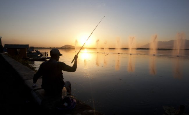 A man is silhouetted as he fishes at sunset on the shore of Dal Lake in Srinagar...