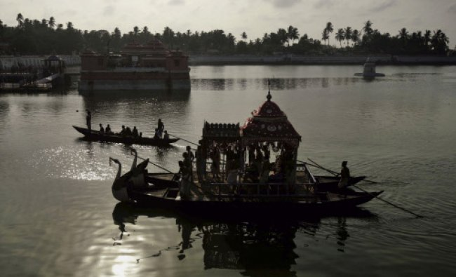Priests carry a deity of Lord Jagannath and perform rituals on a country boat in the ancient ...