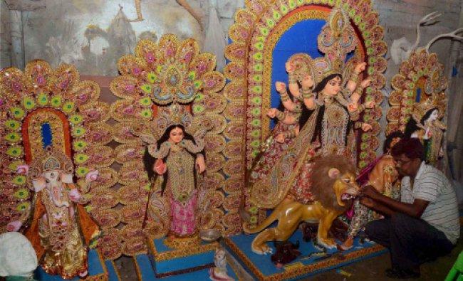 Renowned artist, Prasanta Paul giving finishing touch to the idols of Goddess Durga...