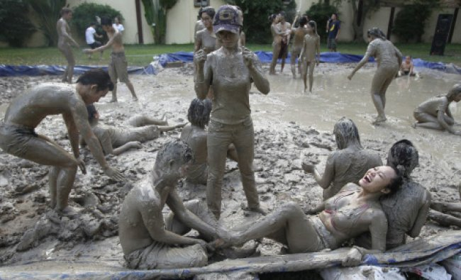 Participants play in the mud during Mud Day celebrations, at the American Club in Hanoi...