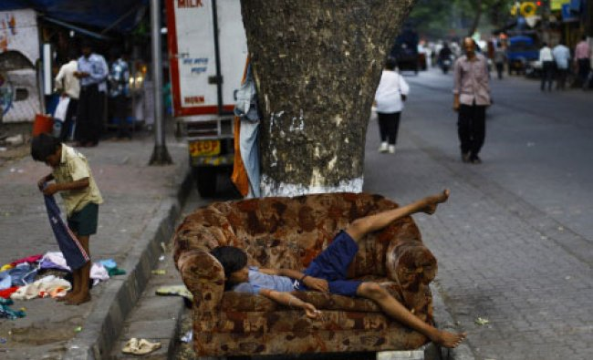 An Indian homeless boy, tries old clothes on a pavement as another takes rest on sofa by a...