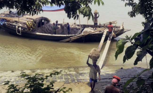 Kolkata: Labors carrying sand to other places after dredging it from River Ganga, in Kolkata on...