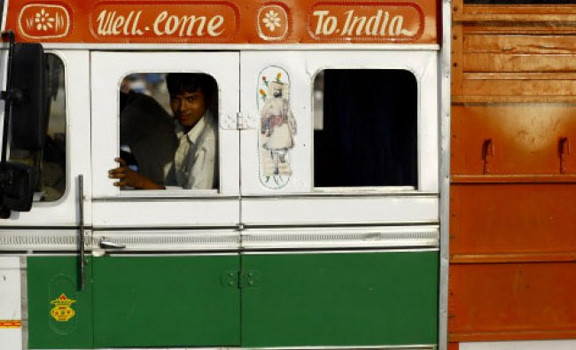 A man looks through the window of a truck painted with the colors of the Indian flag in Mumbai...
