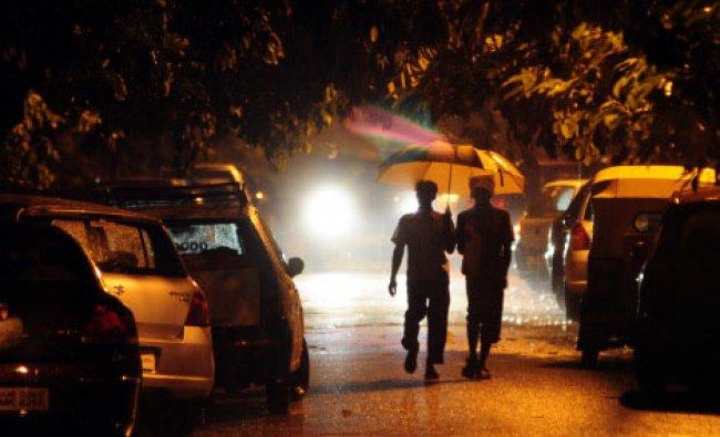 People walk in heavy rain in Bangalore on Sunday night...