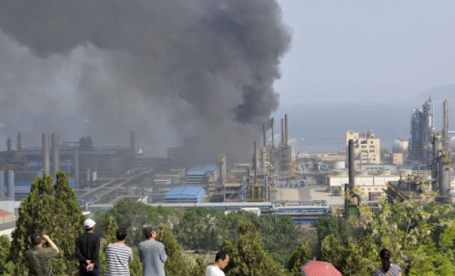 People watch as smoke rises after explosions at a PetroChina refinery in Dalian...
