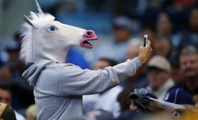 A baseball fan wearing a unicorn mask takes a picture of himself with his phone as he attends...