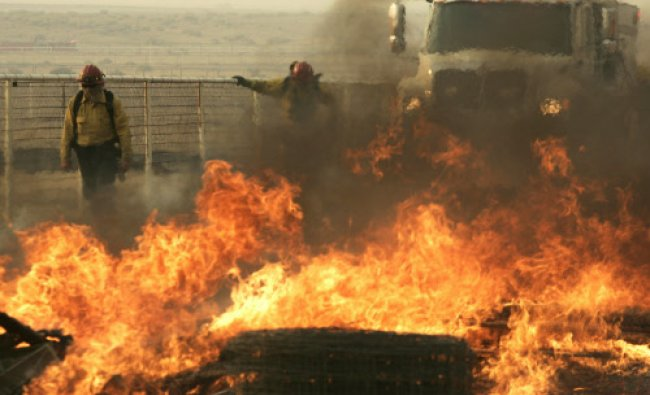 A firefighter monitors flames from a wildfire burning at a horse ranch in Lancaster...
