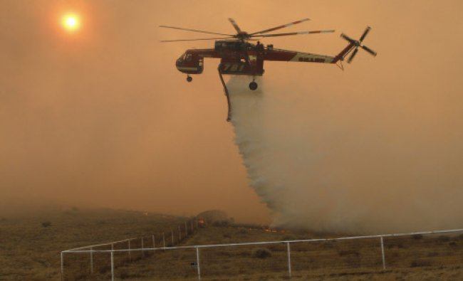 A firefighting helicopter drops water on a wildfire burning in Lancaster, California...