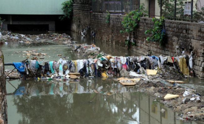 A huge quatity of garbage mixed with plastic and cloth blocking the water flow at Raja Kaluve...