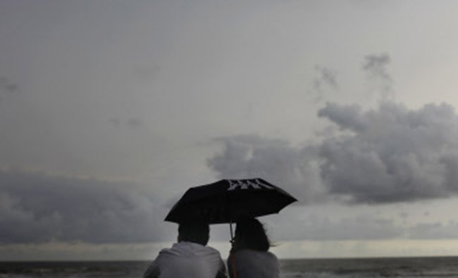 A couple sit along the shores of the Arabian Sea on a cloudy day, in Mumbai...