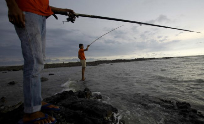 Boys try to catch fish along the shores of the Arabian Sea as rain clouds dot the sky...