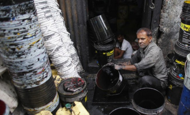 A worker cleans a used paint bucket at a recycling factory in Mumbai...