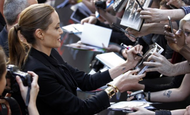 Movie star Angelina Jolie signs autographs at her arrival for the French premiere of the movie...