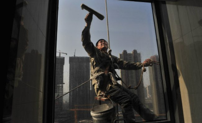 A labourer cleans the window of an office building near a residential complex (back) under ...