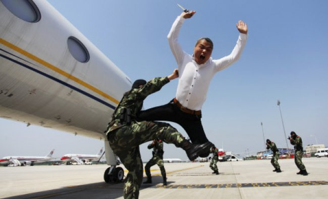 A paramilitary policeman knocks down a man role-playing as a plane hijacker during...