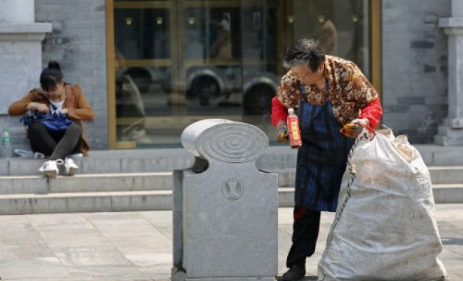 A garbage collector picks up a plastic bottle from a trash can in Beijing May 2, 2013.